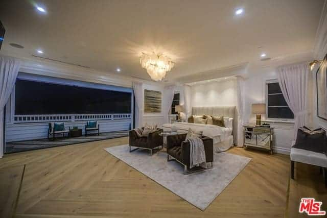 This is a large primary bedroom that has a Farmhouse-style wide hardwood flooring and a large wall that opens up to a balcony. The wide beige ceiling has recessed lights on the sides and the a large decorative lighting in the middle over the sitting area by the foot of the bed.