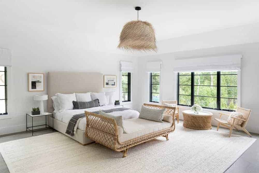 The light gray bed that has a large light gray cushioned headboard is paired with a bedroom bench made of rustic woven rattan at the foot of the bed. This matches with the sitting area chairs, coffee table as well as the hood of the pendant light.