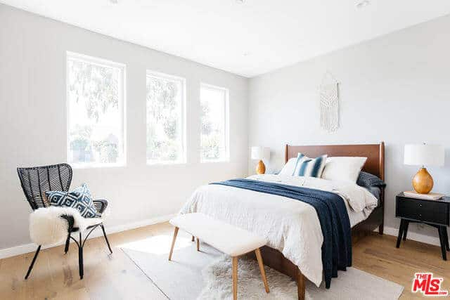 This bright bedroom has white walls and a white ceiling that are brightened even further by the natural lights coming in from the row of windows on the side of the dark wooden bed. This is counterbalanced by the hardwood flooring and the black wooden bedside drawers of the dark wooden bed.