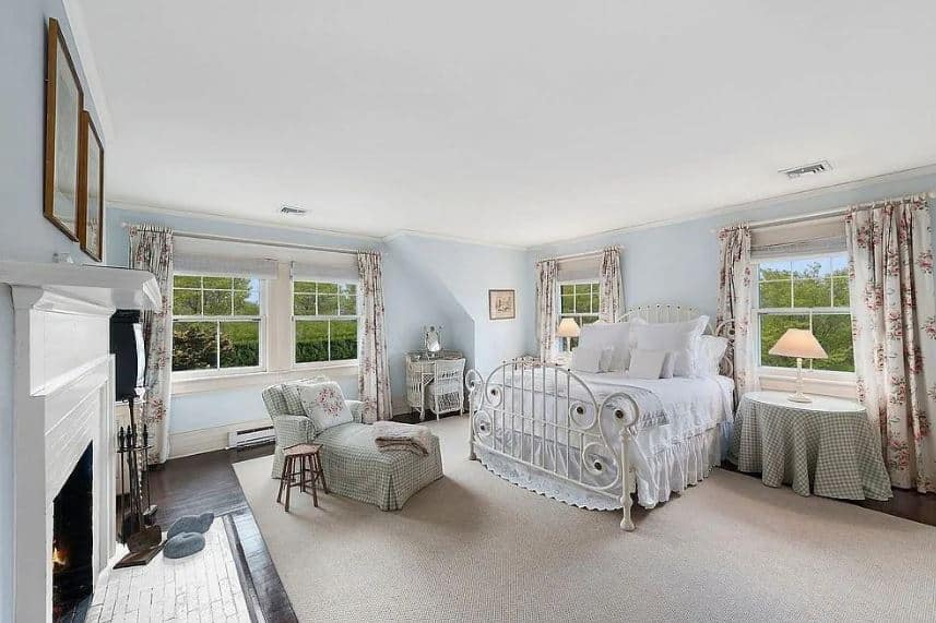This beautiful Farmhouse-style bedroom has bright blue walls that are complemented by the white ceiling and the natural lights coming in from the windows. This is mirrored by the white wrought iron bed across from the white mantle of the fireplace.
