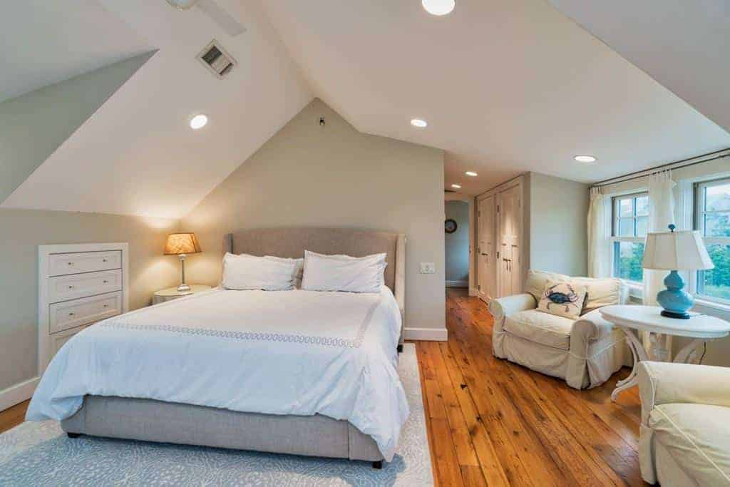 This comfortable bedroom has an irregular arch to its white ceiling that has multiple recessed lights. This is complemented by the light gray walls and contrasted by the hardwood flooring. There is a comfortable sitting area beside the bed that has a couple of cushioned beige armchairs.