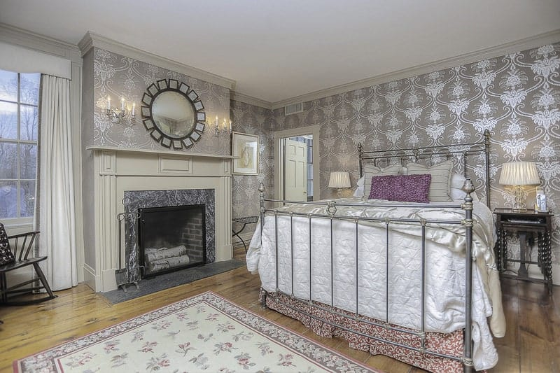 The metal railings of the mission-style bed blend with the subtle silvery patterns of the wallpaper that dominated the walls. This makes the fireplace stand out with its wooden mantle that is adorned with a decorative mirror mounted on the wall above.