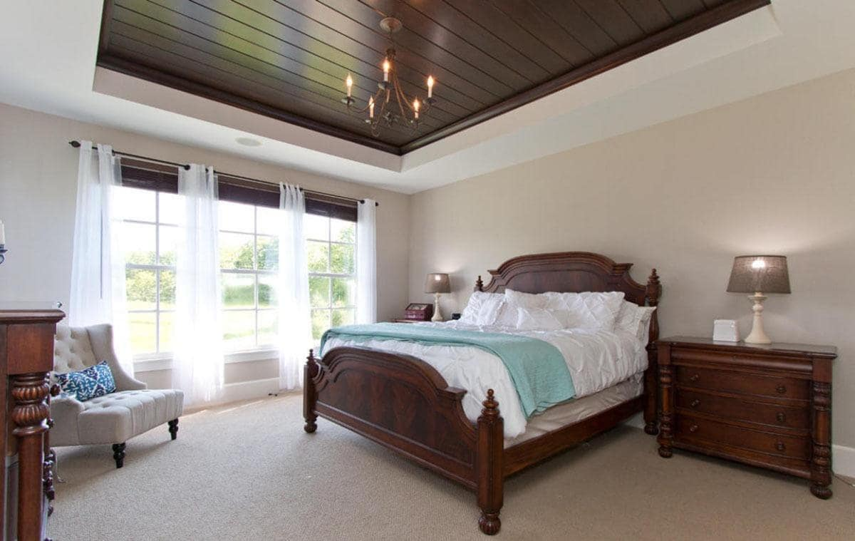 This is a Farmhouse-style bedroom that has a tray ceiling with a dark wooden middle tray matching with the dark wooden sleigh bed and the bedside drawers that flank it on both sides. These are perfectly complemented by the light gray walls and carpeted flooring.