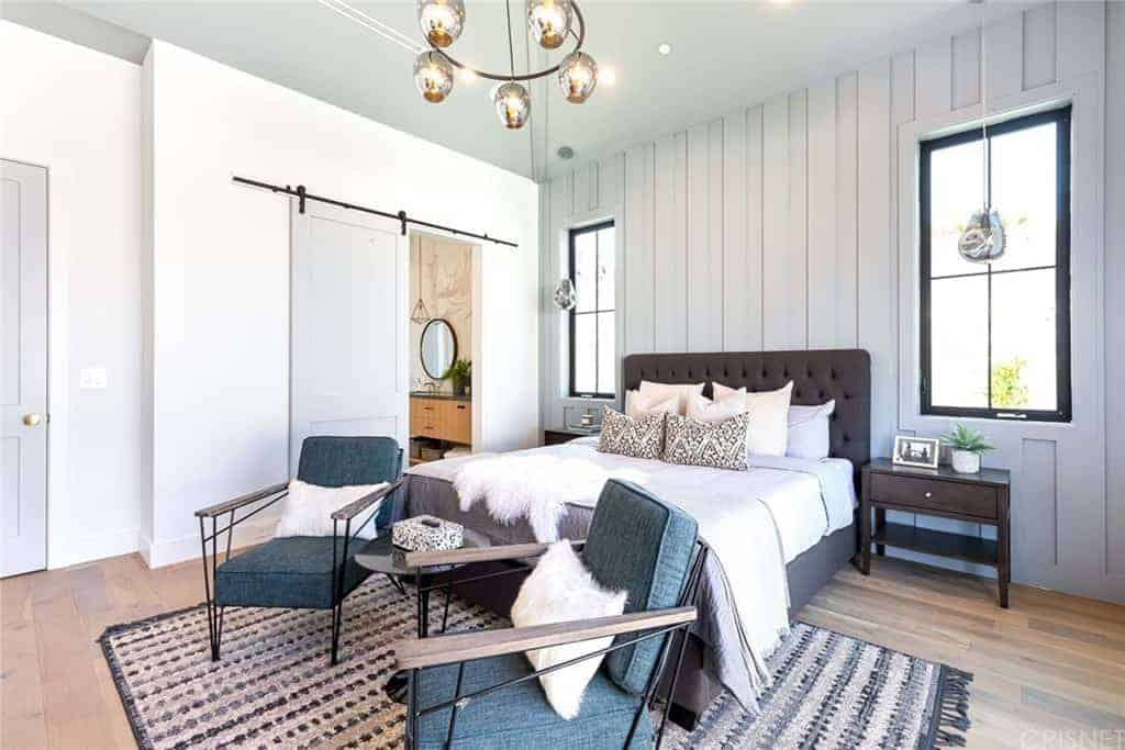 The chocolate brown tufted cushioned headboard of the traditional bed stands out against the white wooden plank finish of the wall behind it. This pairs well with the flanking bedside drawers and the hardwood flooring.