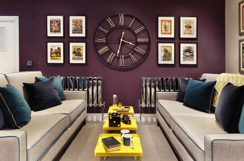 Yellow coffee tables flank by facing sofas stand out in this purple living room designed with black framed posters and an oversized statement wall clock.