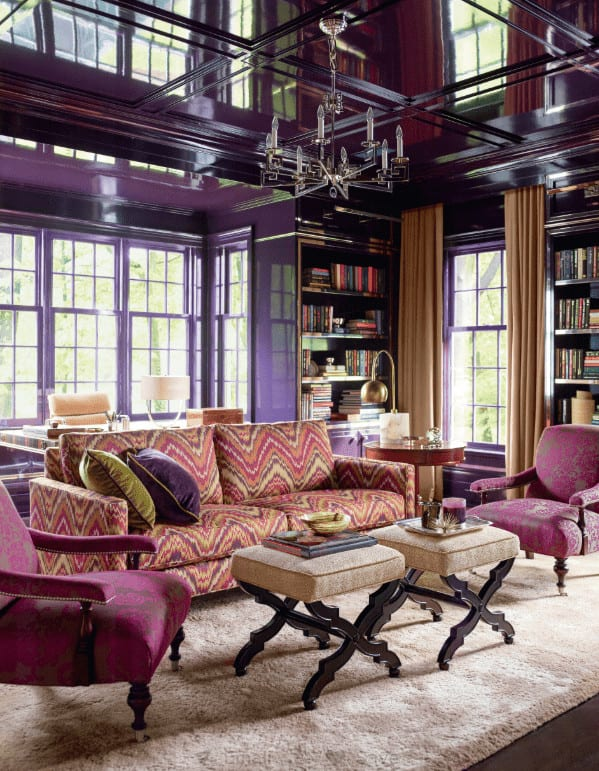 A candle chandelier that hung from the high gloss ceiling illuminates this living room offering an eye-catching patterned sofa accompanied by plum armchairs and beige ottomans that blend in with the area rug.