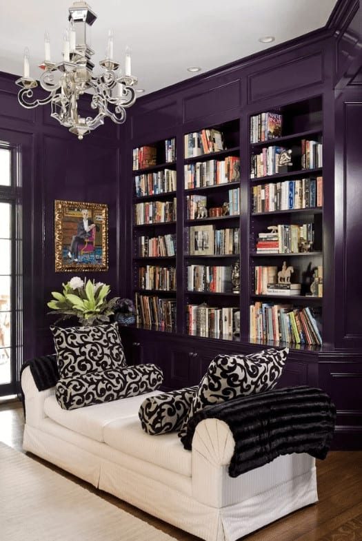 The classic living room features a sophisticated portrait and built-in bookshelves fitted on the wainscoted wall. It includes a glass chandelier and a skirted sofa topped with black patterned pillows.