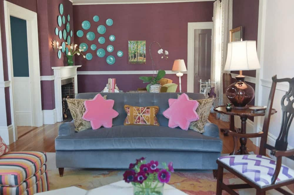 Charming living room with mismatched chairs and a velvet tufted sofa filled with printed and pink star pillows. It has hardwood flooring and purple walls mounted with blue decorative plates.