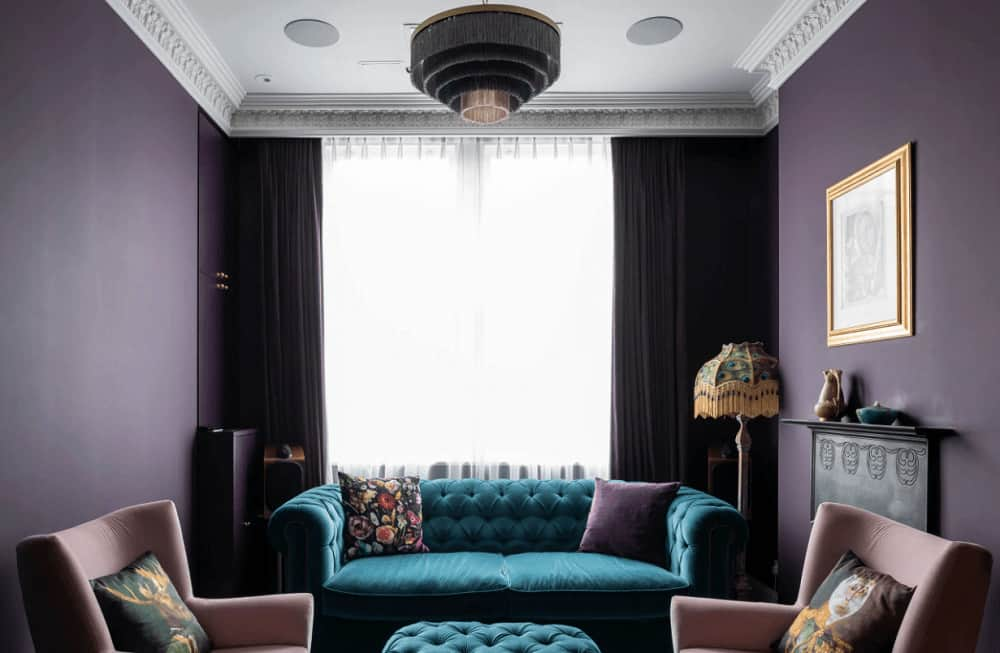 Blue tufted ottoman and sofa stand out in this purple living room boasting wingback chairs and a cascading chandelier that hung from the white ceiling lined with ornate crown molding.