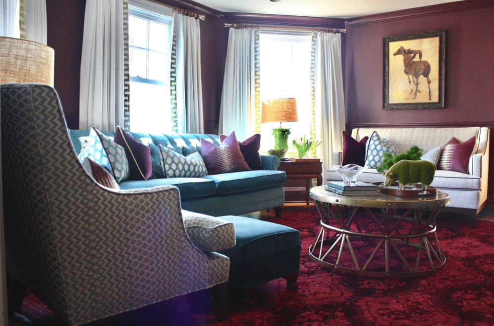 Deluxe living room offers a round coffee table and cozy seats against the purple walls. It has a red patterned rug and classy white curtains covering the glazed windows.