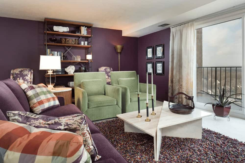 Plaid pillows accentuate the purple sectional sofa that complements the walls. It is accompanied by green armchairs and a stylish coffee table over a shaggy rug.