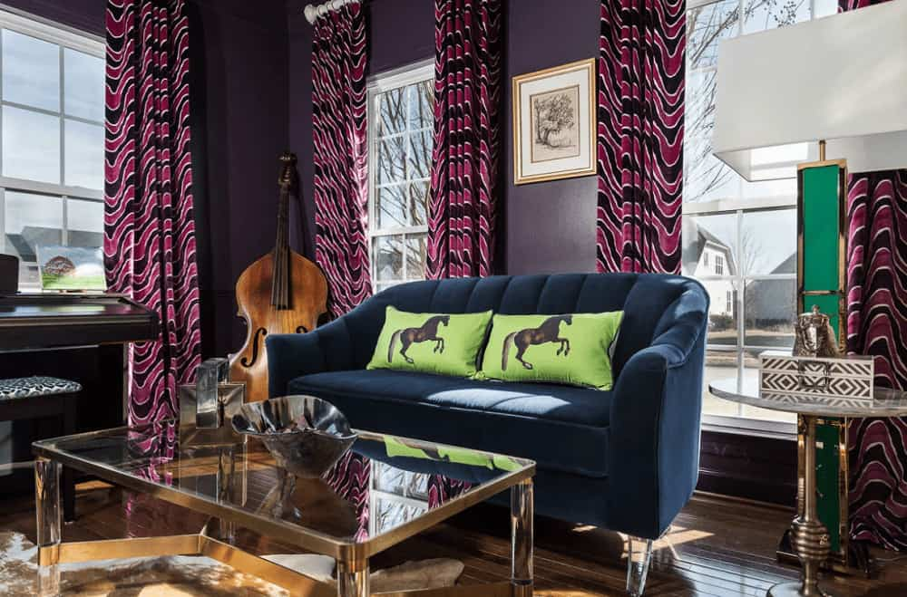 The purple living room showcases a glass coffee table and dark blue sofa accented with lime green pillows that are printed with horses. It has hardwood flooring and white framed windows covered in patterned draperies.