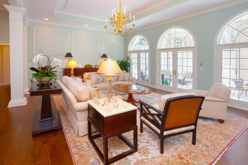 Traditional style living room with tray ceiling, blue walls, white trims and columns, and a gilded chandelier above the seating area facing the French windows.