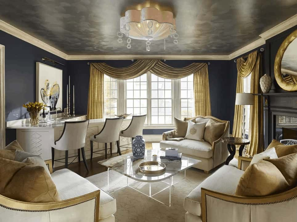 The elegant living room showcases a gorgeous semi-flush mount light and gold classy drapes covering the white framed windows. It includes cushioned chairs and a marble top coffee table facing the bar lined with white stools.