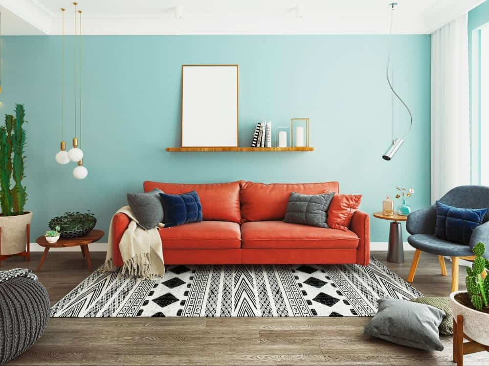 A red sofa stands out in this blue living room offering chrome and bulb pendant lights along with a striking area rug that lays on the natural hardwood flooring.