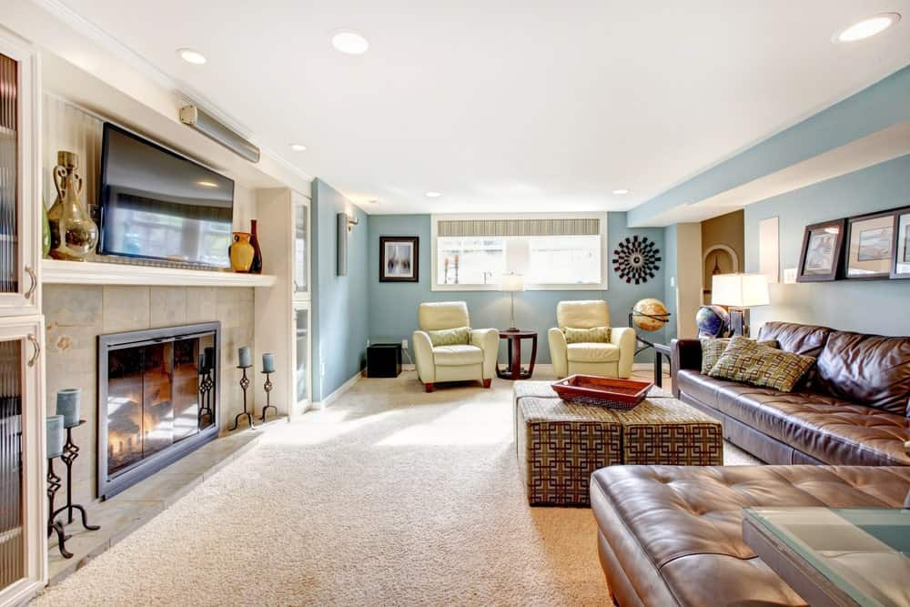 A glass-enclosed fireplace faces the leather tufted sofa paired with a modular ottoman that's topped with a wooden tray. This room has carpet flooring and regular white ceiling mounted with recessed lights.