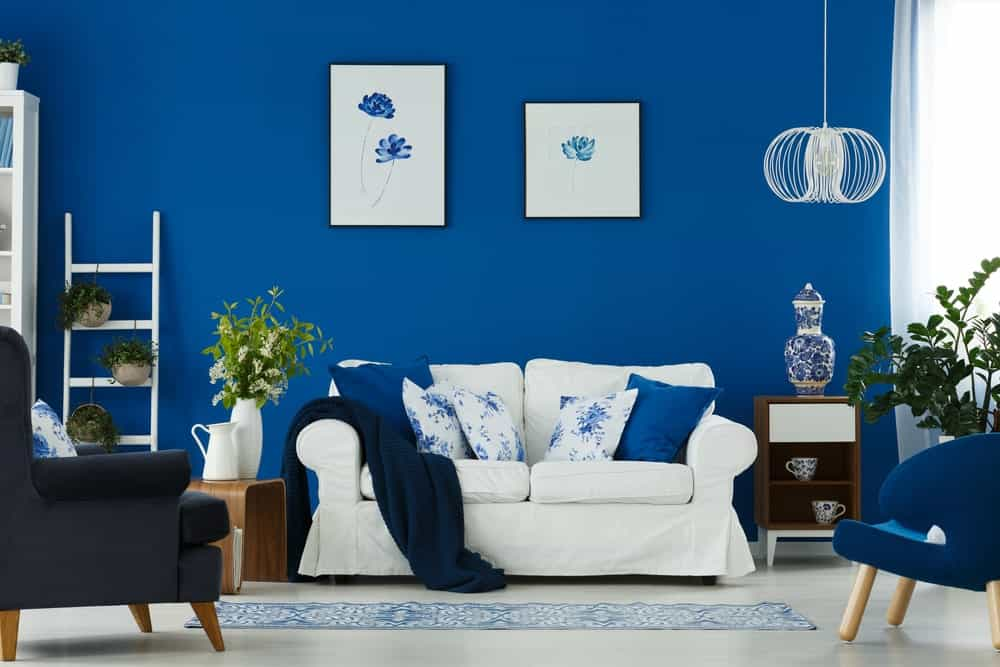 Floral pillows complement the ceramic vase and floral artworks mounted on the blue wall. This room boasts a wire pendant light and mismatched chairs with a patterned runner in the middle.