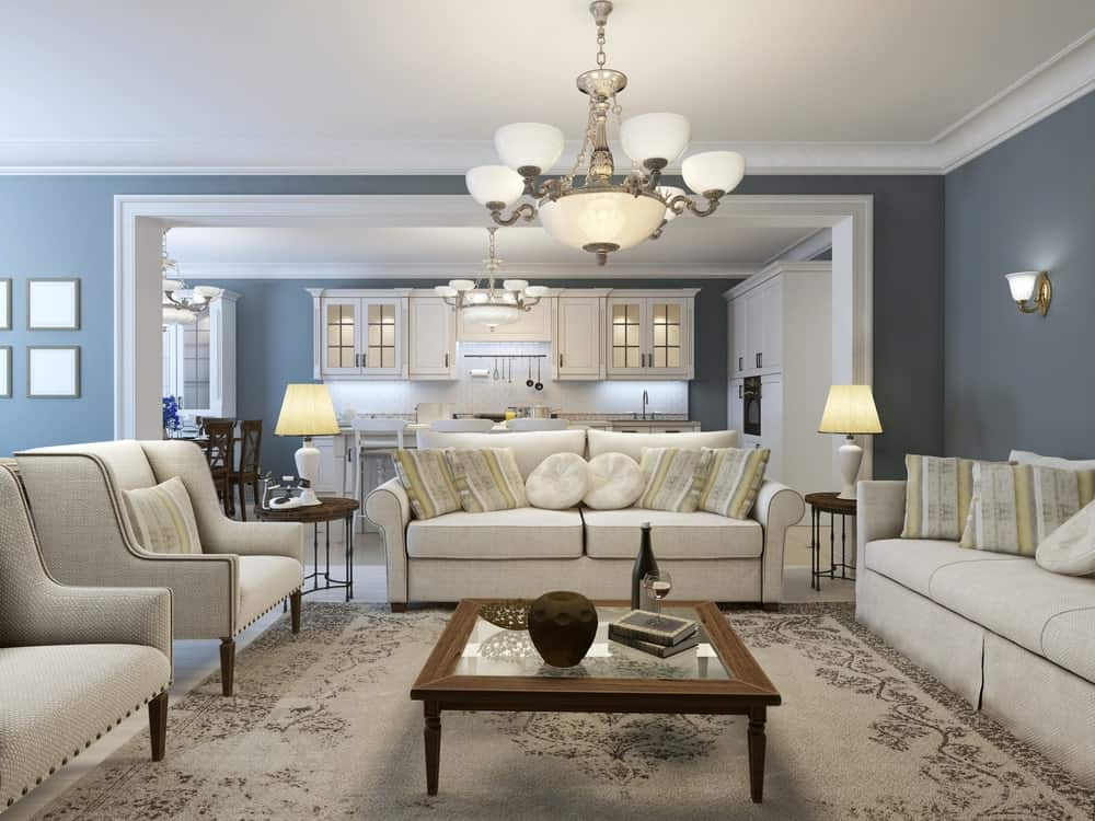 Sophisticated living room illuminated by traditional table lamps and a large chandelier that hung over the glass top coffee table surrounded by beige seats.