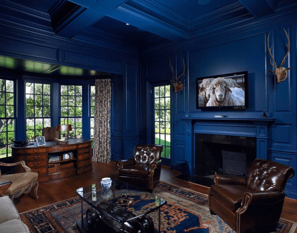 Airy living room with coffered ceiling and full height wainscoting mounted with stag head decors. It has cozy seats and an oval desk that blends in with the rich hardwood flooring.