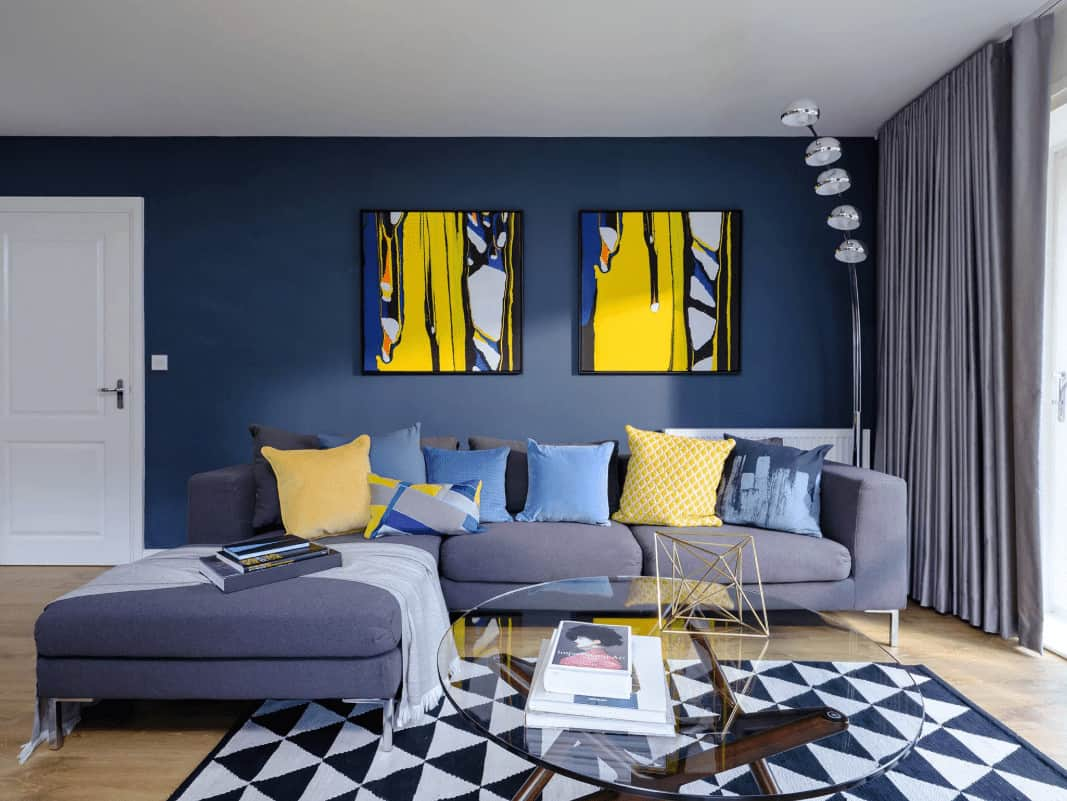 Blue living room decorated with yellow artworks mounted above the L-shaped sofa filled with fluffy pillows. It has a five-head floor lamp and a glass top coffee table that sits on a striking area rug over the light hardwood flooring.