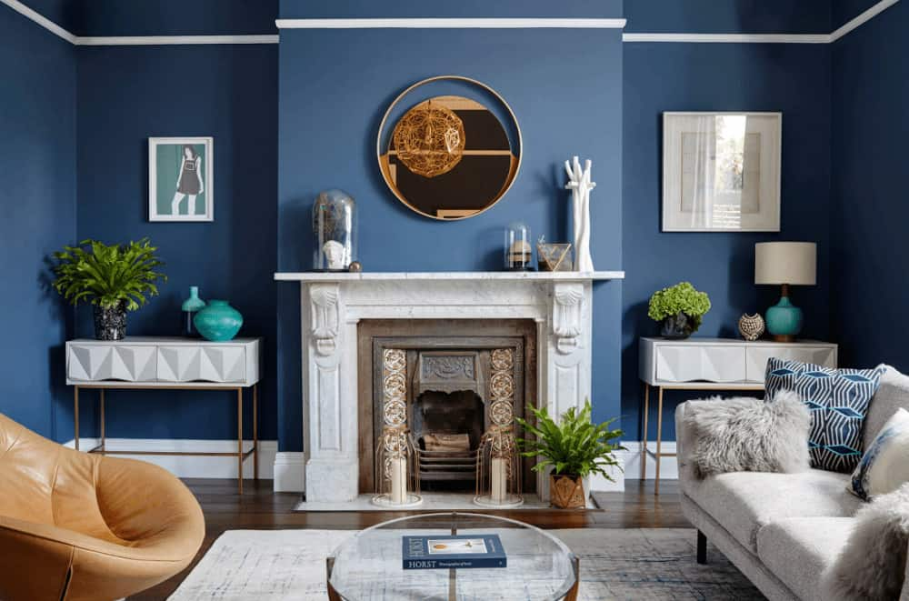 Contemporary living room decorated with white framed wall arts and a round mirror that hung above the marble fireplace flanked by white console tables.