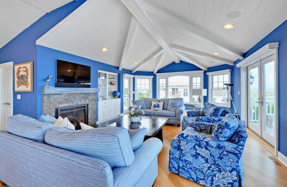 Beach style living room with rich hardwood flooring and shiplap ceiling lined with white beams. It includes a brick fireplace and gorgeous blue seats surrounding a dark wood coffee table.