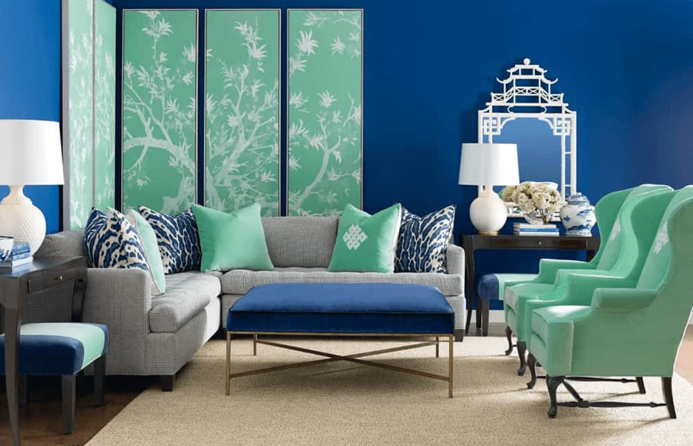 Blue living room with pops of mint greens from the multi-panel wall art, wingback chair and pillows laying on the gray sofa. It has a cushioned coffee table and dark wood side tables topped with white lamps.