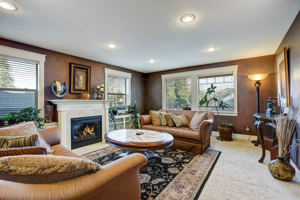 Large formal living room with brown leather couches and an elegant centerpiece table set on a classy rug on top of the carpeted flooring. There's a fireplace on the side of the room as well.