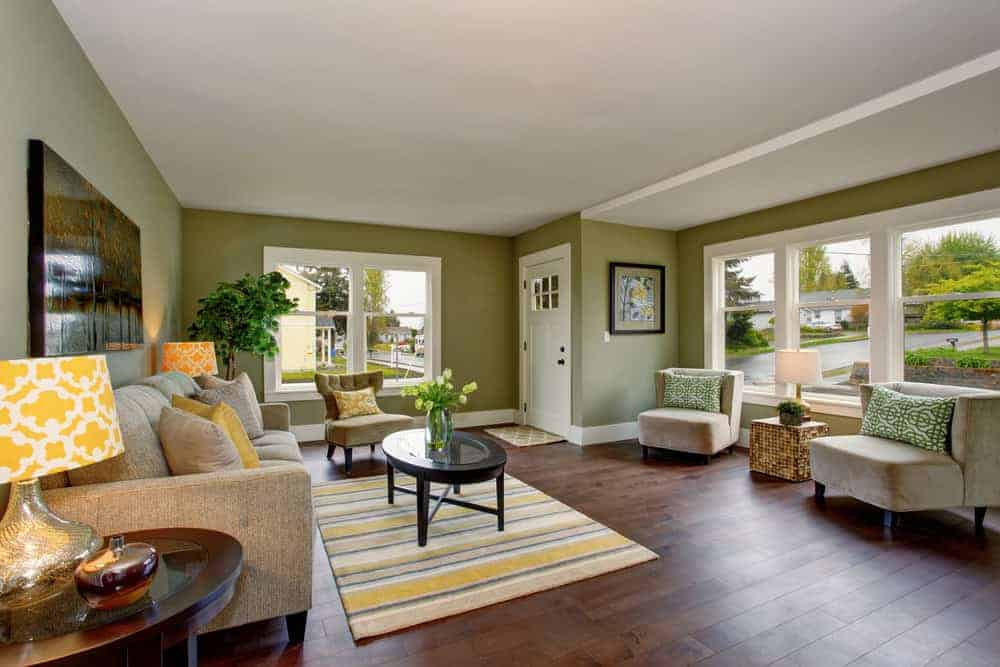 A spacious Country-style living room with olive green walls and hardwood flooring, along with a cozy sofa set and a small center table on top of an area rug.