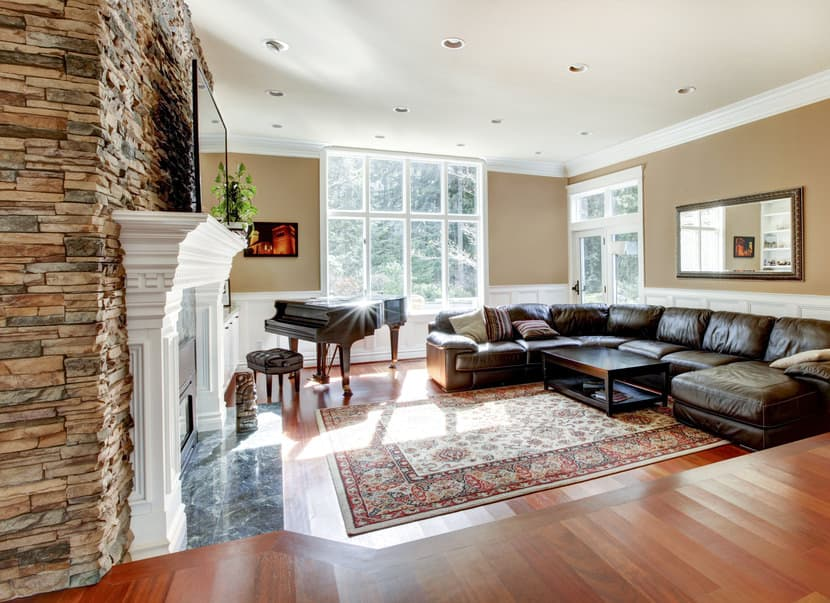 A spacious formal living room with a large fireplace and has a large flat-screen TV on top of it. The room has a piano on the side and a large leather couch as well.