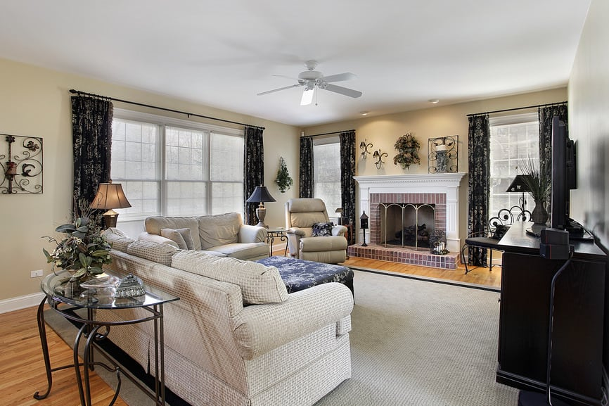 Large formal living room featuring a comfortable sofa set and a large area rug covering the hardwood flooring. The area offers a large widescreen TV and a large fireplace.