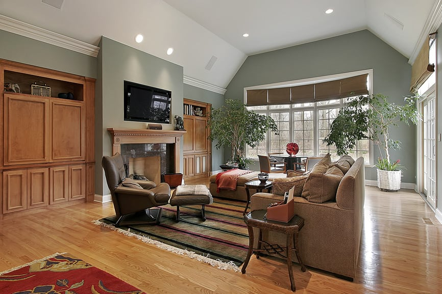 Huge formal living room boasting a cozy sofa set and a large fireplace with a flat-screen TV on the wall.