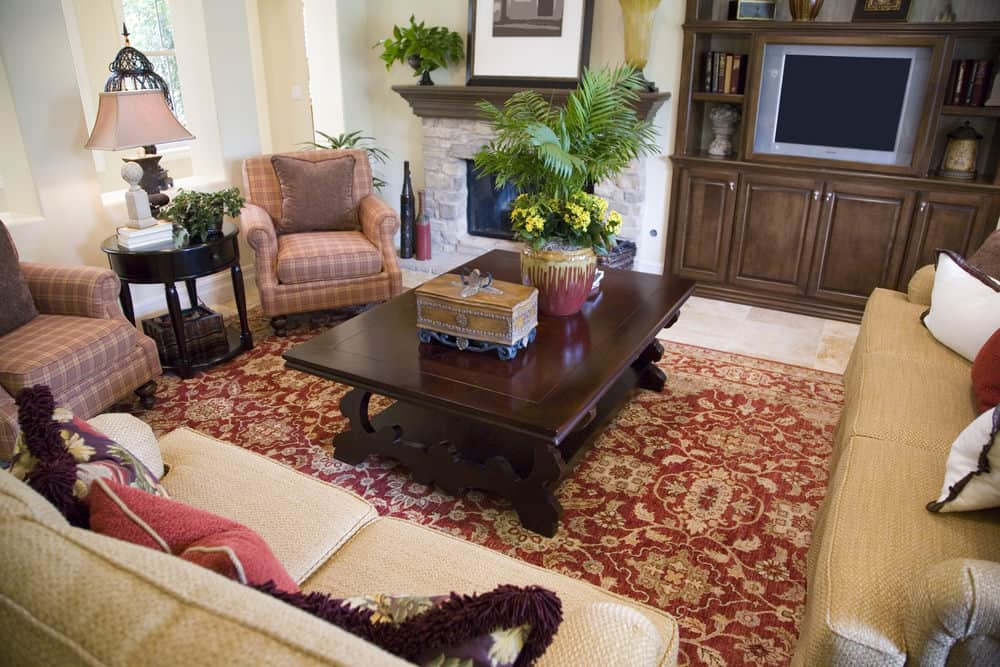 A focused shot at this formal living room's classy sofa set and a center table situated on top of a red area rug. The area has a fireplace.