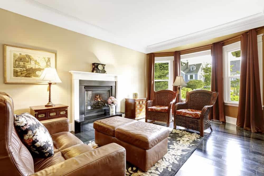 A Country-style formal living room boasting a large brown leather seat with a large ottoman in front, set on a stylish area rug covering the dark hardwood flooring. The room also offers a fireplace.