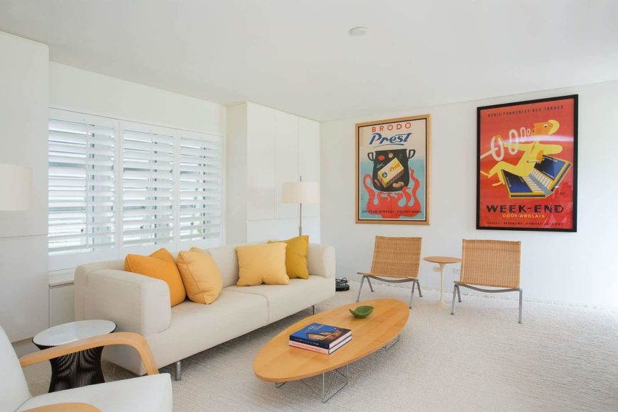 White living room decorated with large posters that are mounted above the wicker chairs.  It has an oval coffee table and a sleek sofa accented with amber pillows.