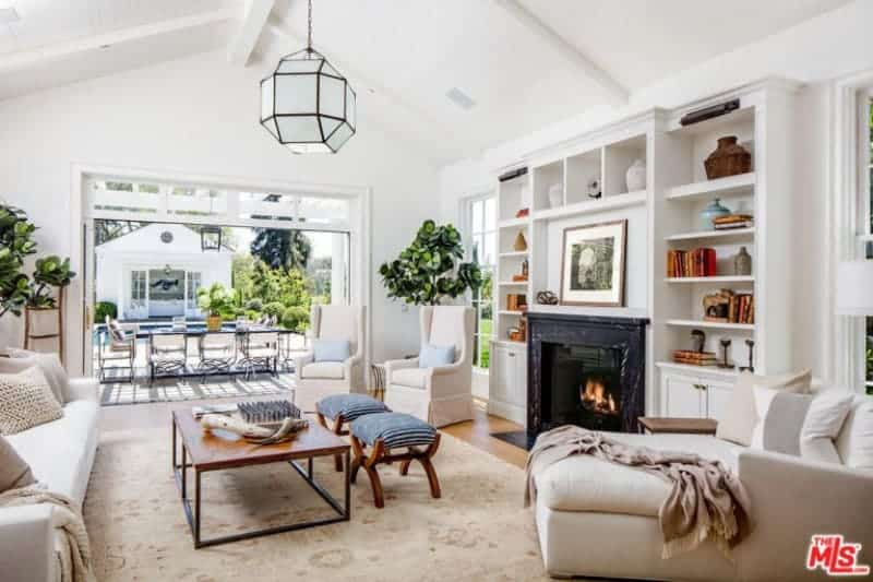 White living room contrasted by a black fireplace that's surrounded with open shelving. It has beige seats and a wooden coffee table with striped stools on the side lighted by an octagonal pendant light.
