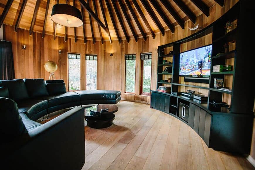 A round living room with a curved sectional sofa in black leather paired with a modular coffee table that faces the TV and cabinet. This room has wide plank flooring and wood beam ceiling mounted with a drum pendant light.
