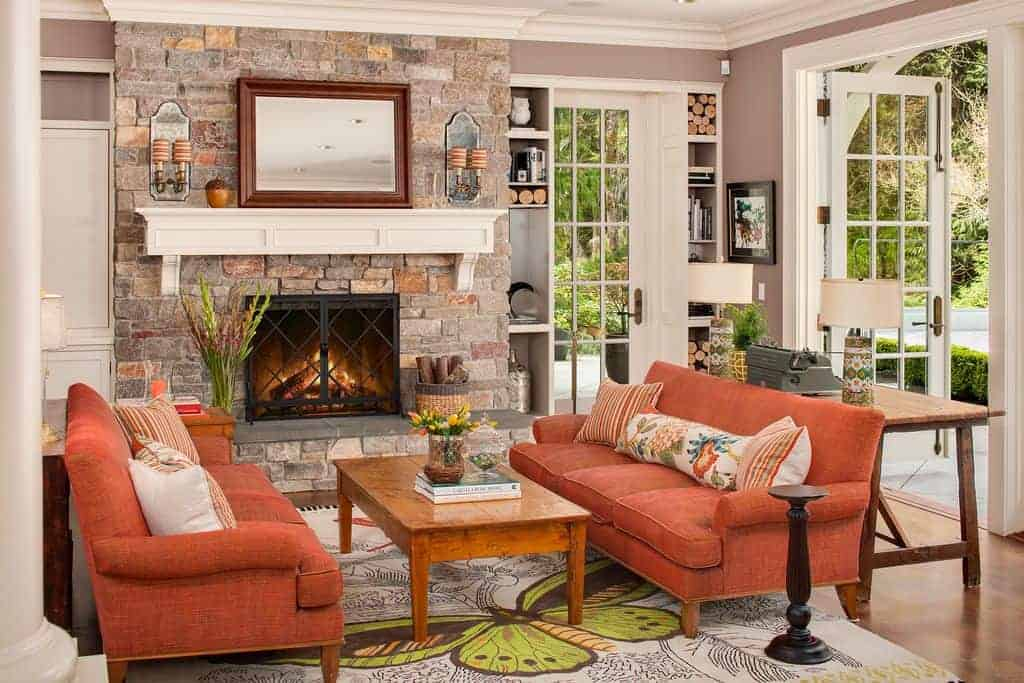 Orange sectional sofas flank a wooden coffee table facing the stone brick fireplace lined with a white mantel. This room has built-in shelving and glazed doors leading out to the yard.