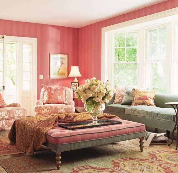 Clad in pink striped wallpaper, this living room features mismatched seats and a tufted ottoman topped with a throw blanket and large flower vase.