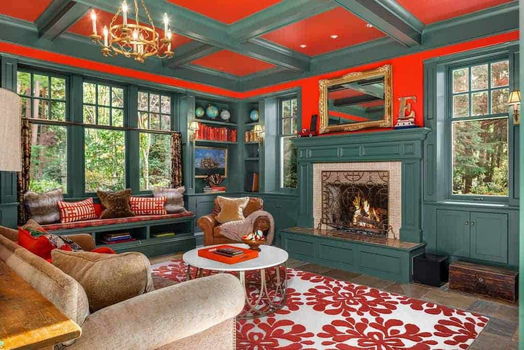 A stylish coffee table sits on a floral area rug complementing with the red pillows and cushion fitted on the window seat nook. This room has a fireplace and brown sofa lighted by a brass chandelier that hung from the coffered ceiling.