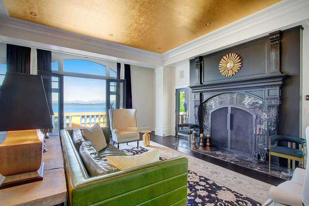 Fabulous living room with a green sofa and black fireplace decorated with a sunburst mirror. It has a gold ceiling and French door leading out to the balcony with a spectacular beach view.