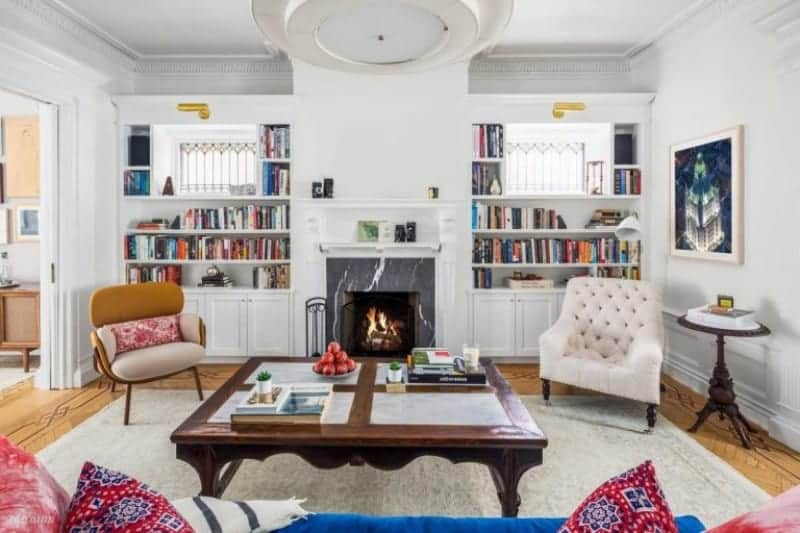 A cozy sofa faces the wooden coffee table and fireplace accompanied by mismatched armchairs. It is flanked by built-in shelvings filled with books.