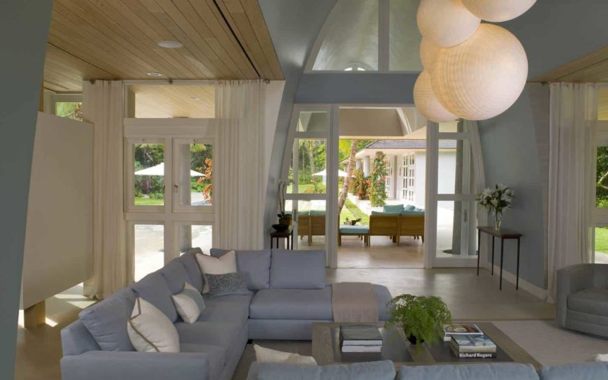 Oversized round pendants hang over the wooden coffee table accompanied by blue sectional sofas and gray armchair. This room has a vaulted ceiling and glass slider that opens to the porch.