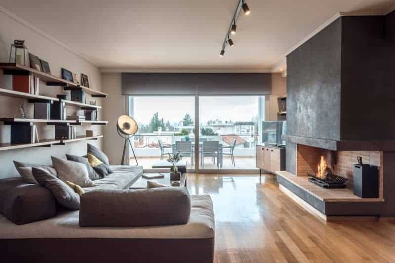 An L-shaped sofa is situated under the floating shelves filled with books and decors. It faces the open fireplace with a flat-screen TV on the side sitting on a wooden console table.