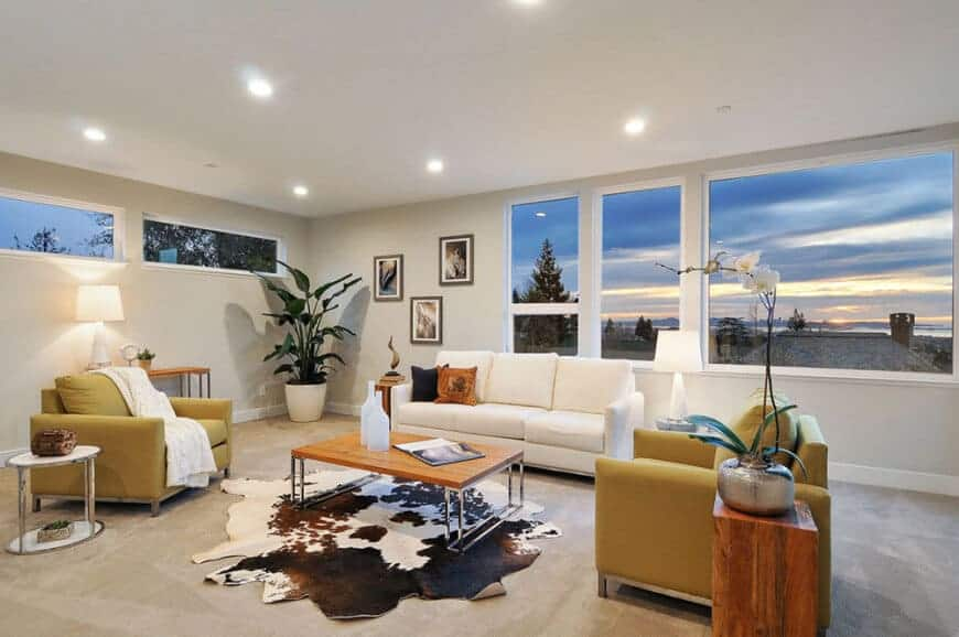 White living room with a sectional sofa and yellow armchairs surrounding a wooden coffee table on a cowhide rug illuminated by recessed ceiling lights.
