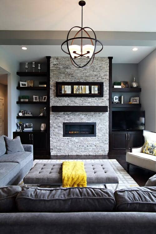 A gorgeous chandelier hangs over the tufted ottoman surrounded with cozy seats and a fireplace fixed on the brick pillar. It is accompanied by built-in shelvings filled with frames and decors.