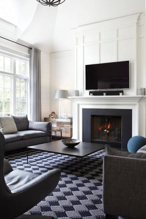 A checkered area rug adds a striking contrast to the white walls mounted with a flat-screen TV. This room features sleek seats and a metal coffee table that faces the fireplace.