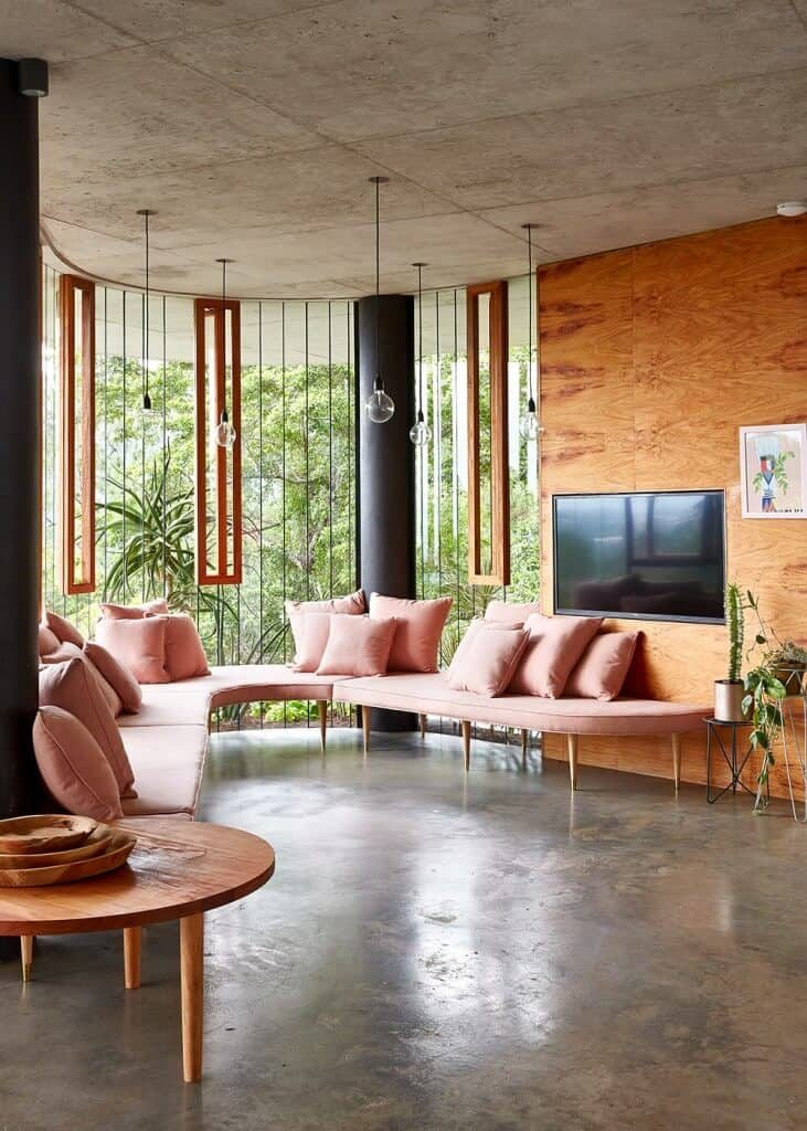 Airy living room with a curved sofa and fireplace fitted on the wood paneled wall. It has concrete flooring and a distressed ceiling mounted with bulb pendant lights.