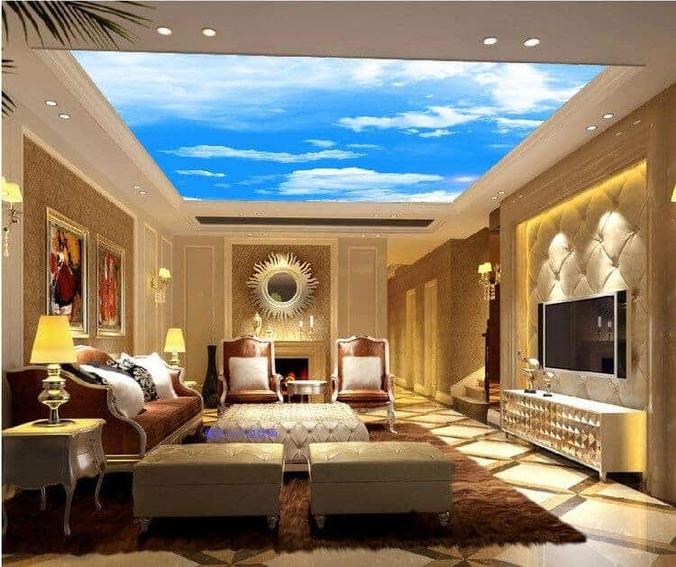 Elegant living room with a stunning sky ceiling and tiled flooring topped by a brown area rug. It has classy seats and a flat-screen TV mounted on the beige tufted wall.