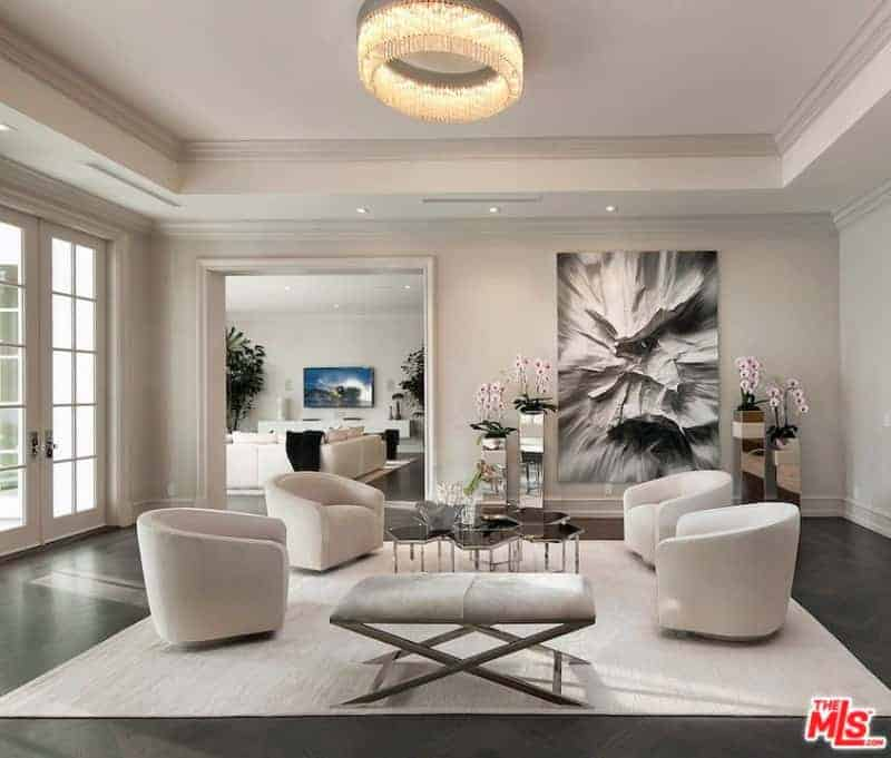 A fancy round chandelier illuminates this living room boasting a cushioned bench and round back chairs that surround a honeycomb coffee table. It is decorated with a black and white painting along with potted flowers that sit on mirrored pedestals.